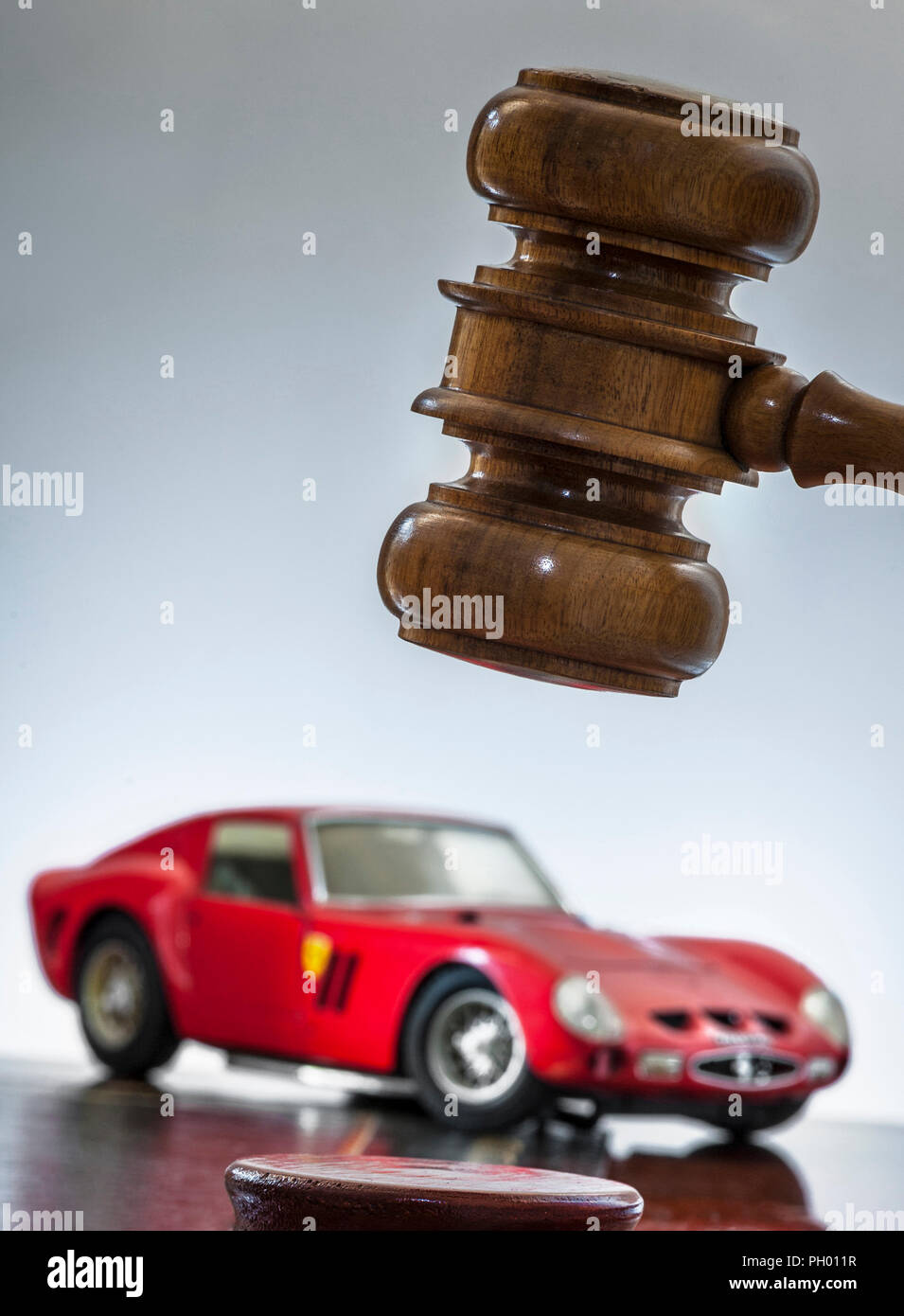 1963 Ferrari 250 GTO with auctioneers hammer in sale-room auction situation Concept image of classic renowned red vintage Ferrari with auction hammer - Stock Image