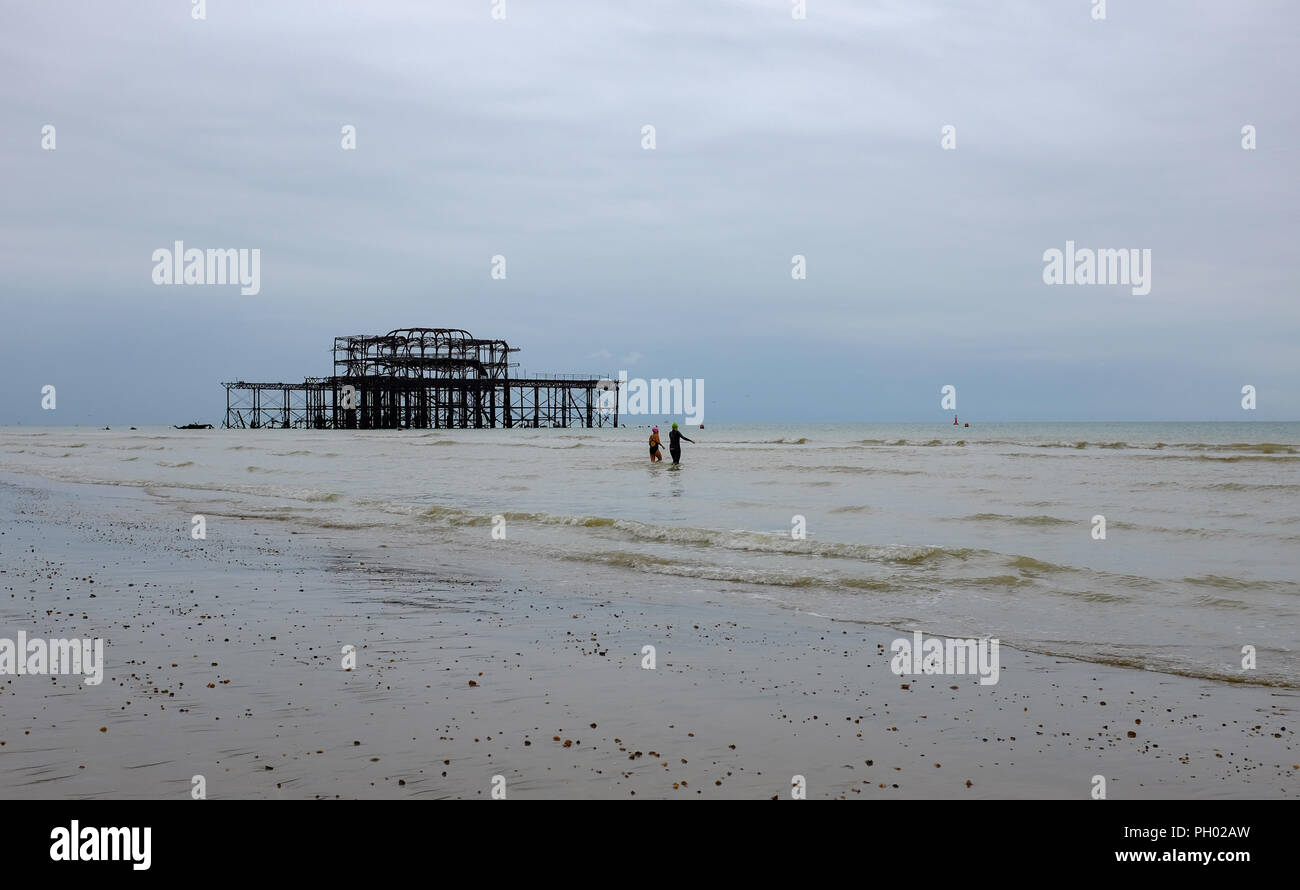 Brighton UK 29th August 2018 - Early morning swimmers head into the sea by the West Pier in Brighton on a dull grey day but the weather is forecast to improve again by the weekend with temperatures expected to reach  the mid twenties in the South East Photograph taken by Simon Dack Credit: Simon Dack/Alamy Live News - Stock Image