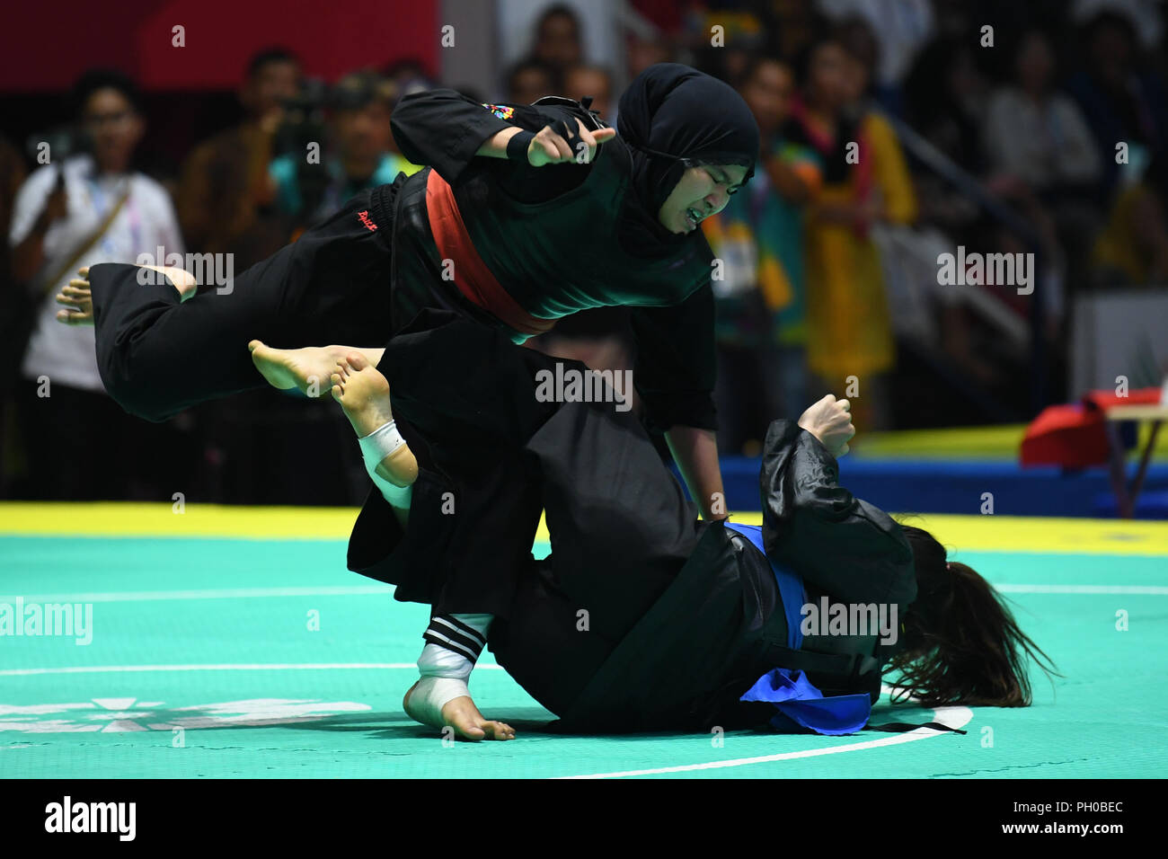 Jakarta, Indonesia. 29th Aug, 2018. Pipiet Kamelia of Indonesia (L) competes during the Pencak Silat Women's 60kg to 65kg gold medal match agaisnt Nguyen Thi Cam Nhi of Vietnam at the 18th Asian Games in Jakarta, Indonesia, Aug. 29, 2018. Credit: Pan Yulong/Xinhua/Alamy Live News - Stock Image