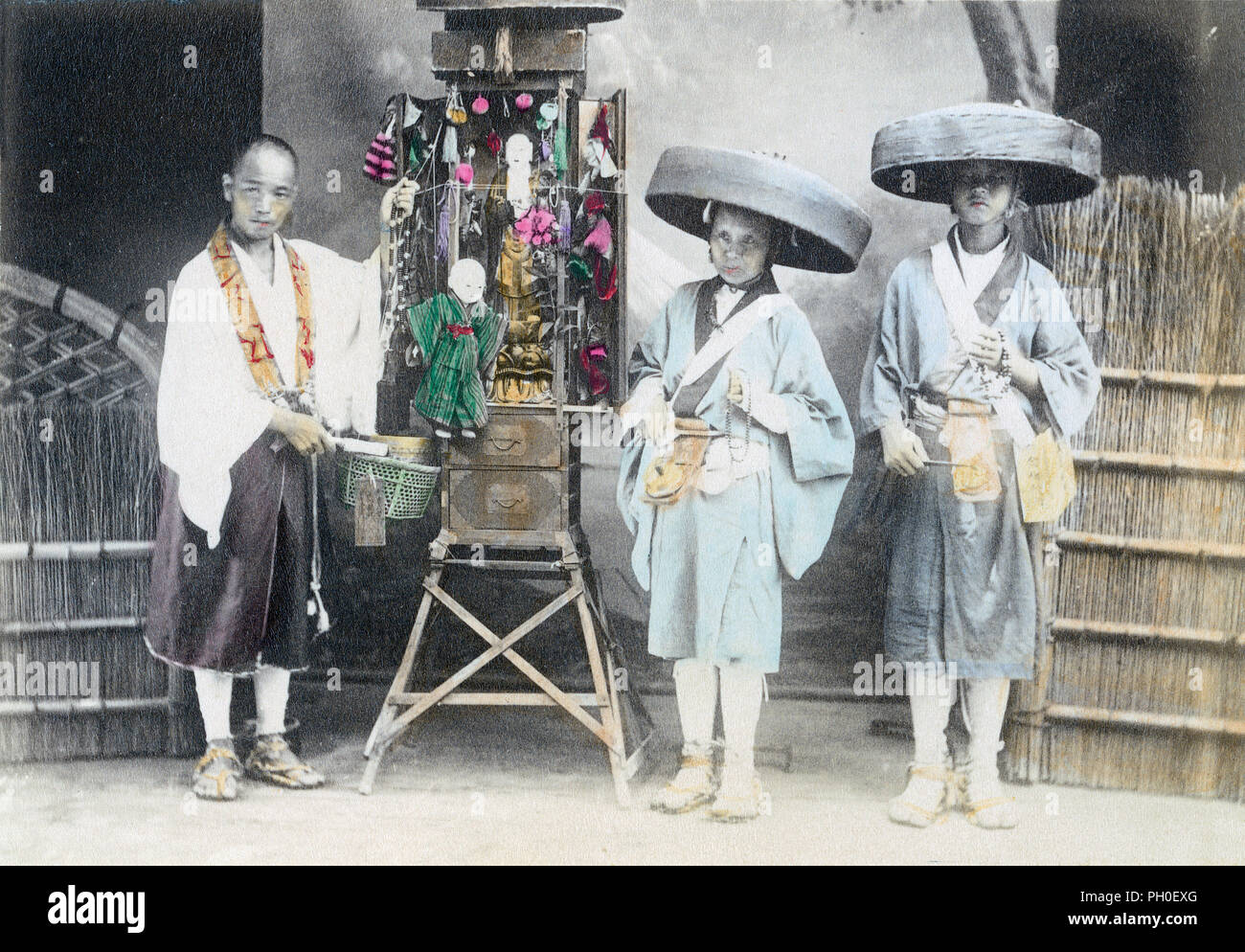 [ 1890s Japan - Pilgrims with a Portable Buddhist Shrine ] —   Three pilgrims with a portable Buddhist shrine. The two people on the right wearing kaki (bamboo hats) are pilgrim beggars known as Hachitataki. They would move from house to house, stand at the front entrance and chant while ringing the bells hanging from their belt.  The original image is small, so this photo doesn't lend itself well for very large usages.  19th century vintage albumen photograph. - Stock Image