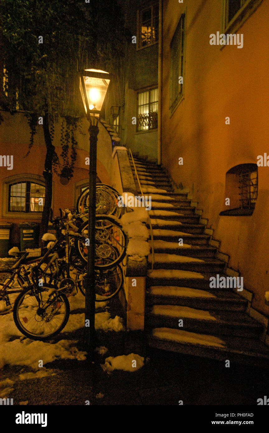 Chained up bicycles in a small courtyard with sone- covered flight of steps in Mehlplatz, Graz old town, Austria. Stock Photo