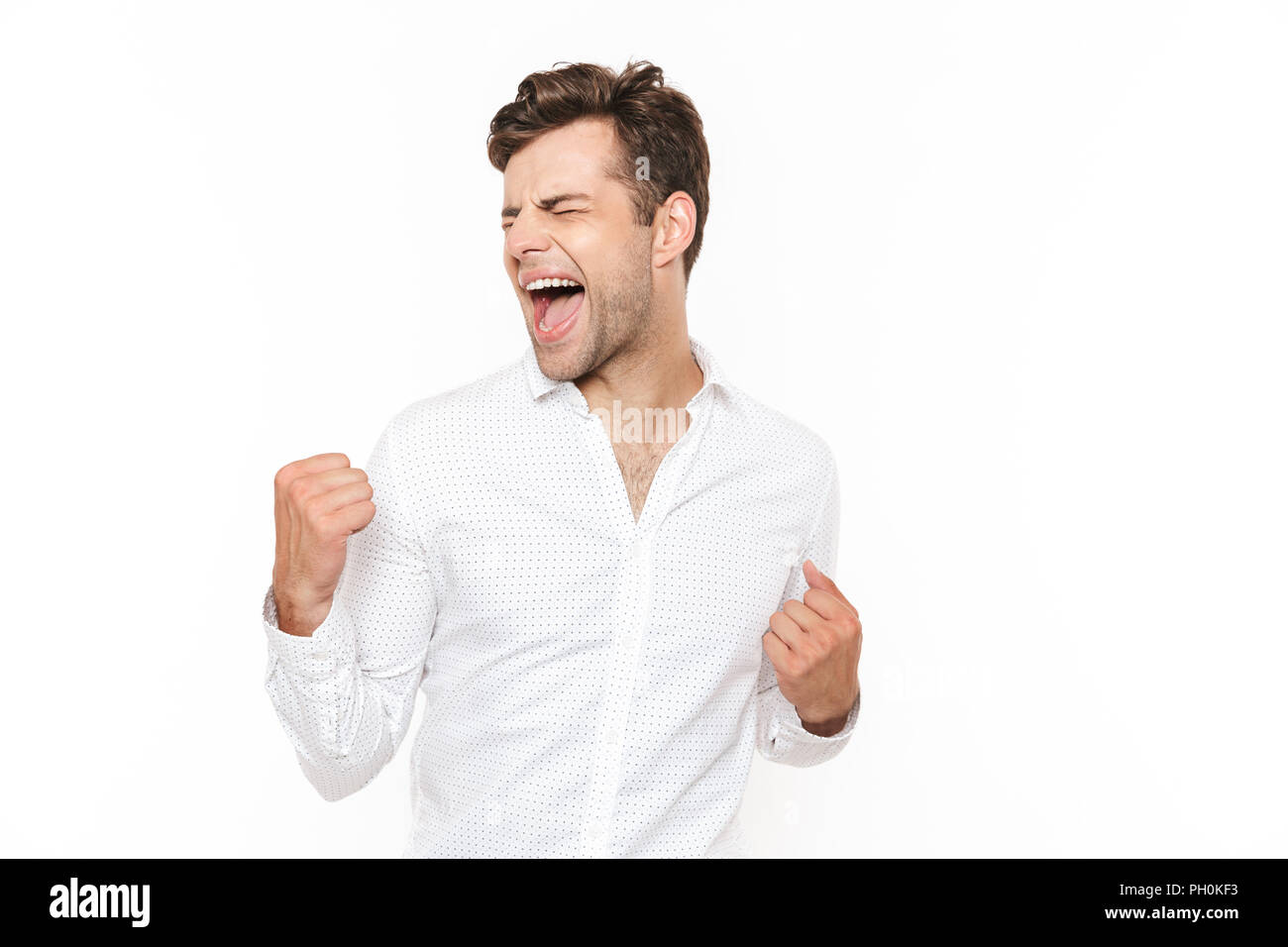 Photo of happy man 30s rejoicing and clenching fists isolated over white background - Stock Image