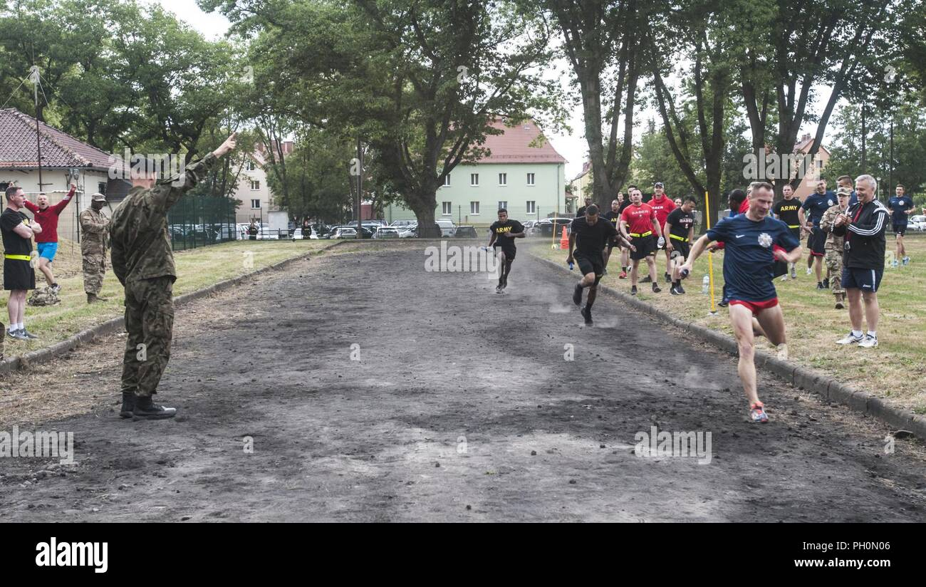 A 23rd Artillery Brigade, Polish Land Forces soldier crosses the finish line first during the 4x400 relay race held in celebration of the 243rd Army Birthday celebration held at the Polish Land Forces base in Boleslawiec, Poland, June 14, 2018. U.S. Soldiers assigned to the 91st Engineer Battalion, 1st Armored Combat Brigade Team, 1st Calvary Division, and Company B, 151st Expeditionary Signal Battalion, South Carolina National Guard, placed second and third. Stock Photo