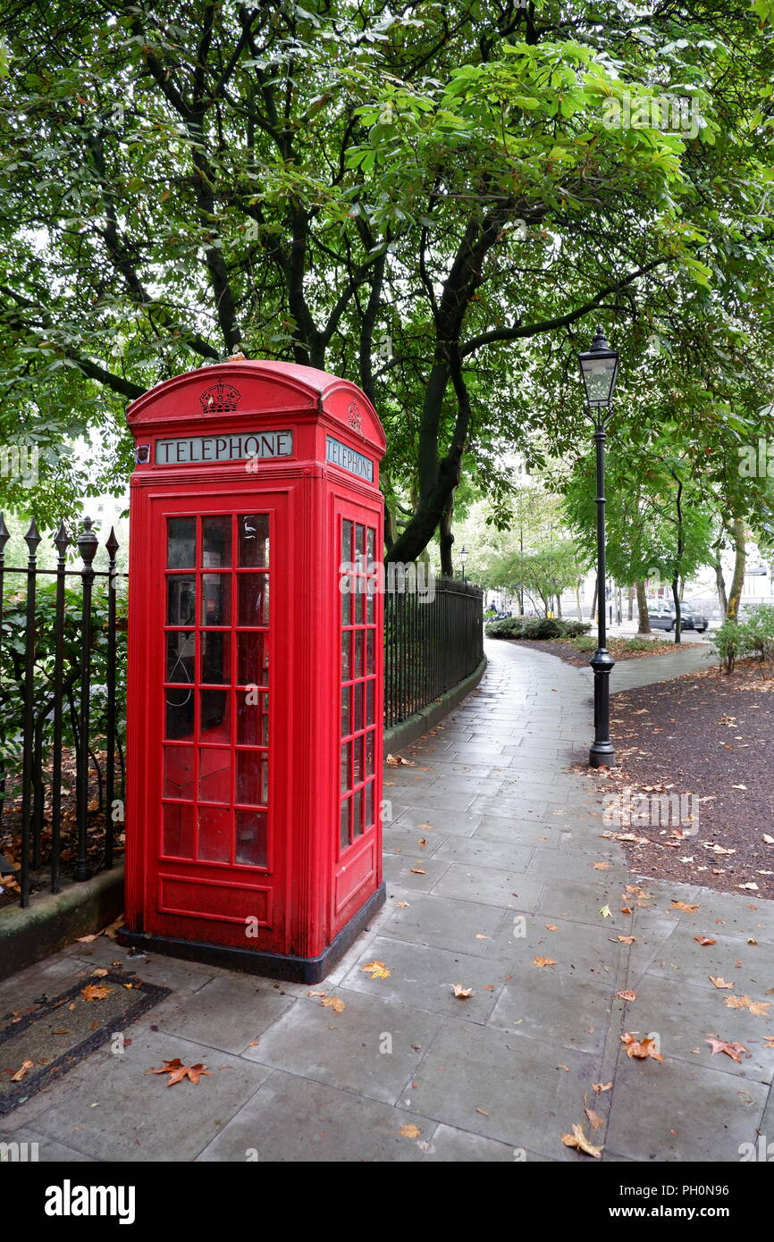 A red telephone box in London (UK).  The telephone kiosk is for public use and was designed by Sir Giles Gilbert Scott, - Stock Image