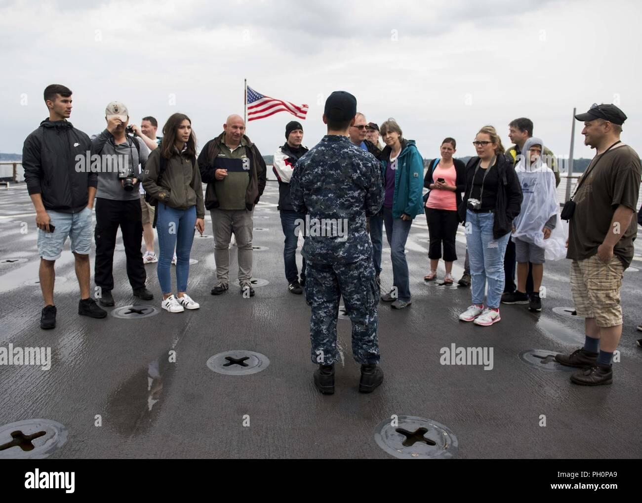 SEA (June 16, 2018) Hospital Corpsman 2nd Class Andy Kim, center, gives a tour of the Harpers Ferry-class dock landing ship USS Oak Hill (LSD 51) in Kiel, Germany, during Kiel Week 2018, June 16. Oak Hill, home-ported in Virginia Beach, Virginia, is conducting naval operations in the U.S. 6th Fleet area of operations. Stock Photo