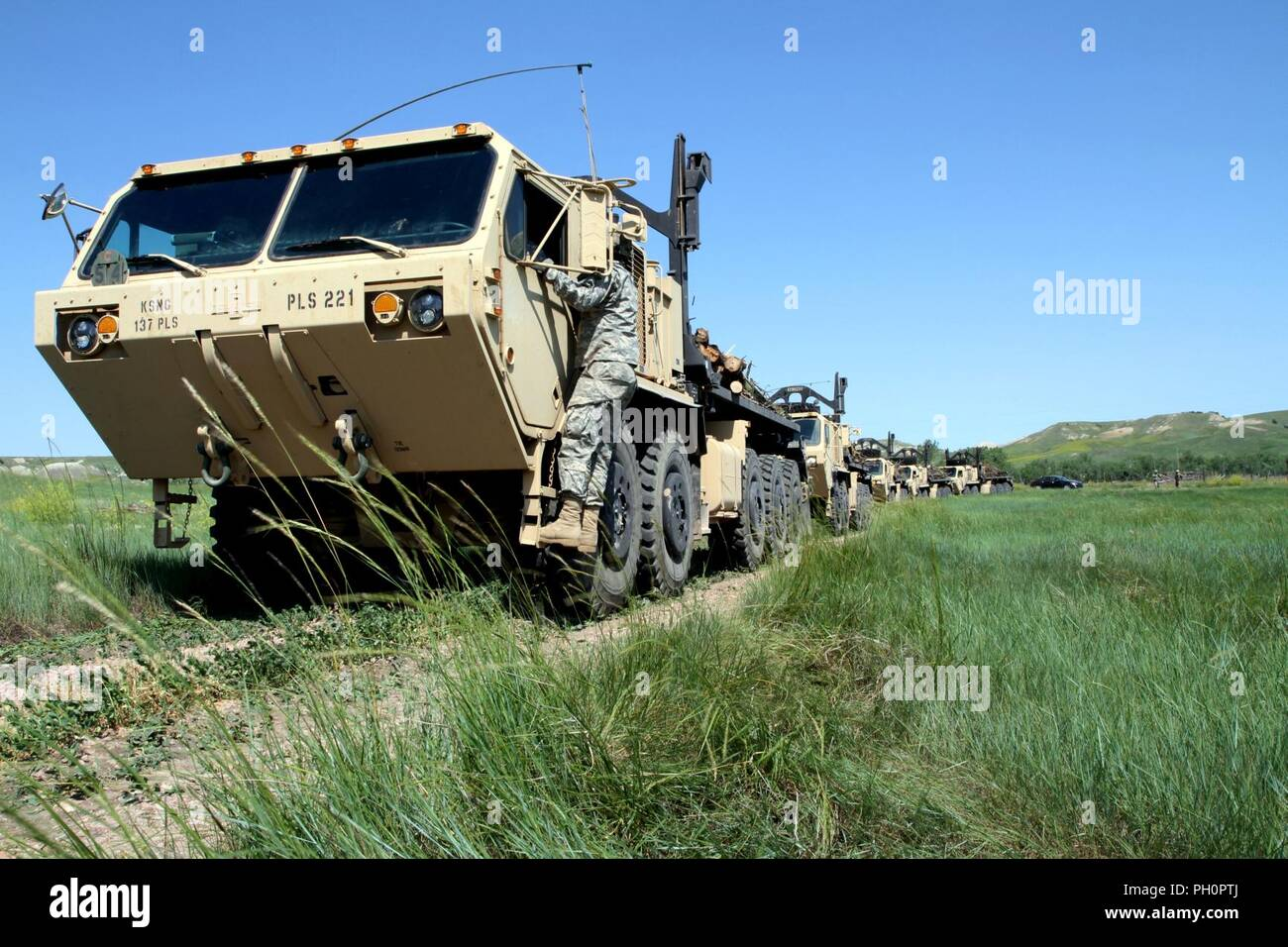 Soldiers from the 137th Transportation Company, Kansas Army National Guard, convoy to Red Shirt, S.D., June 15, 2018. These military vehicles allow large amounts of timber to be delivered to Native American reservations in support of the timber haul operation and Golden Coyote training exercise. Stock Photo