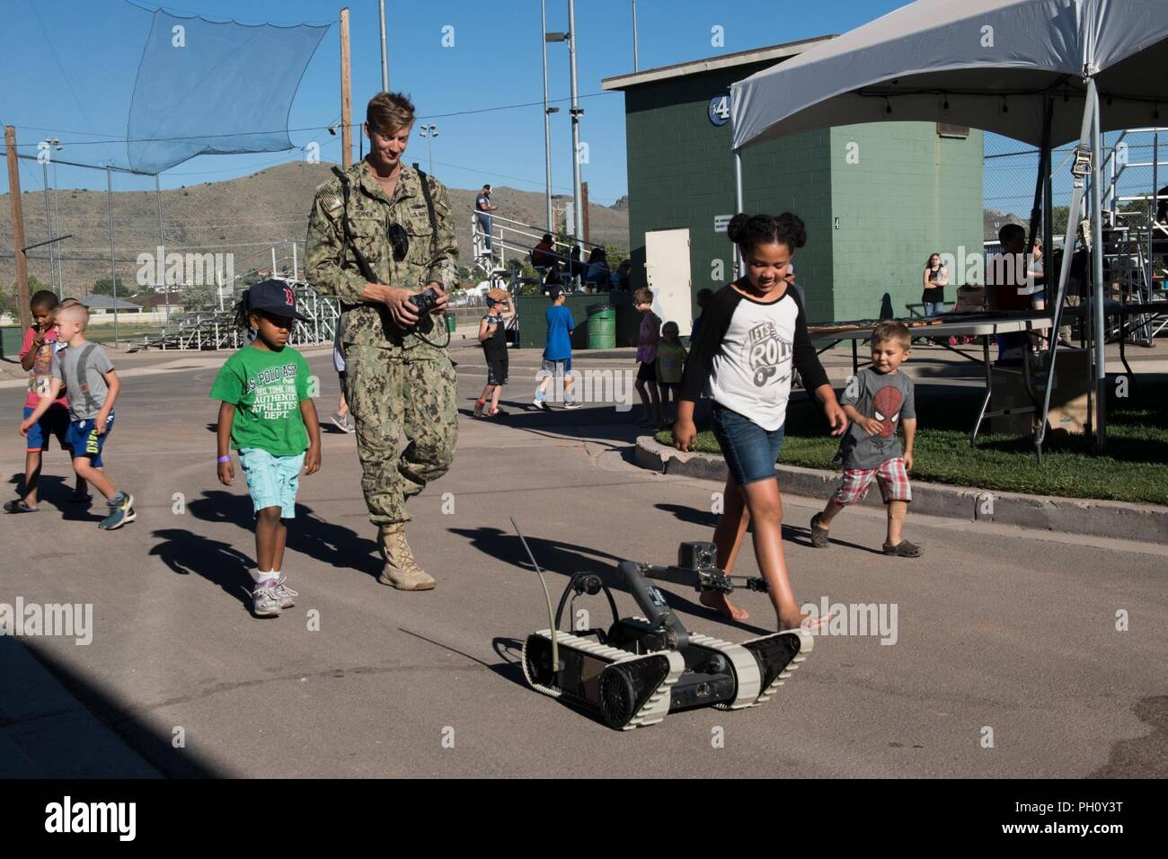 CARSON CITY, Nev. (June 21, 2018) Navy Diver 2nd Class Adam Renner, assigned to Southwest Regional Maintenance Center Alpha Dive Team, demonstrates how to operate an iRobot 310 Small Unmanned Ground Vehicle at a Nevada District 1 Little League Tournament on Governor's Field in support of Reno/Carson City Navy Week.  The Navy Office of Community Outreach uses the Navy Week program to bring Navy Sailors, equipment and displays to approximately 15 American cities each year for a week-long schedule of outreach engagements. - Stock Image