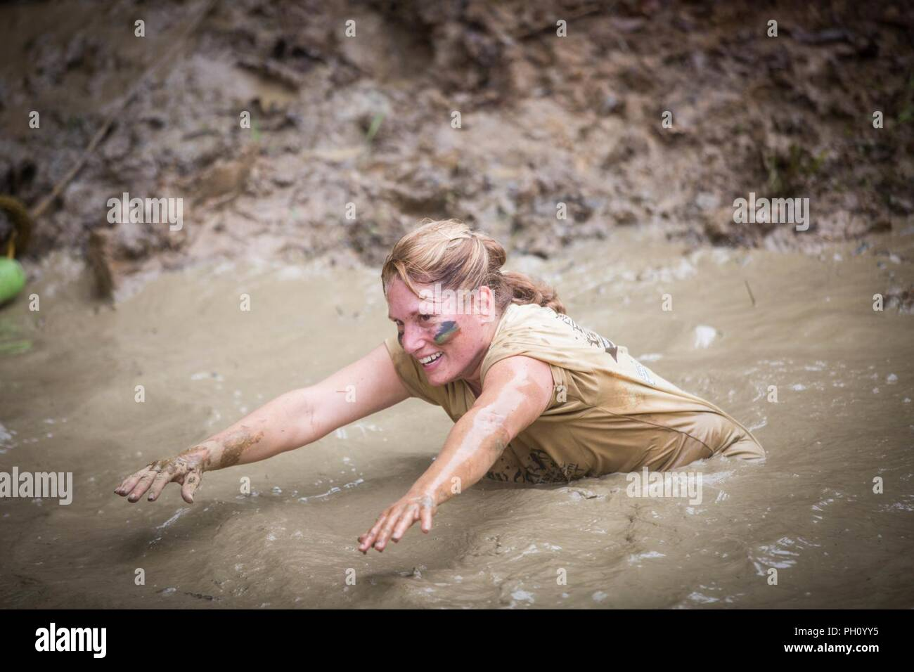Participants run during the annual Marine Corps Marathon (MCM) Run Amuck at Marine Corps Base Quantico, Va., June 23, 2018. The Run Amuck is the MCM's messiest mud and obstacle course consisting of a four-mile trail with 21 challenges to include body weight exercises, rope climbs, and mud pits. - Stock Image