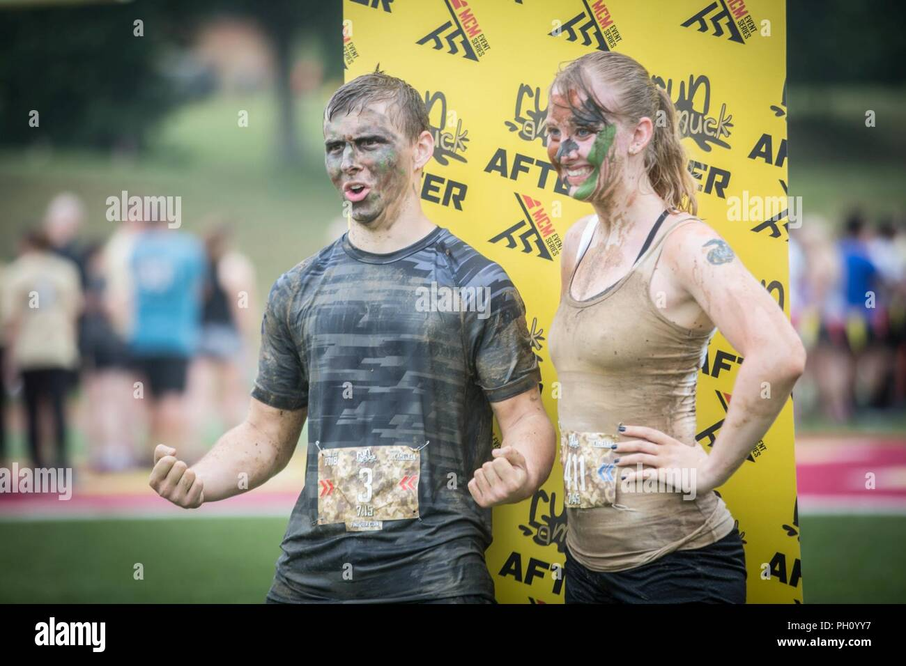 Participants pose for a photo following the annual Marine Corps Marathon (MCM) Run Amuck at Marine Corps Base Quantico, Va., June 23, 2018. The Run Amuck is the MCM's messiest mud and obstacle course consisting of a four-mile trail with 21 challenges to include body weight exercises, rope climbs, and mud pits. - Stock Image