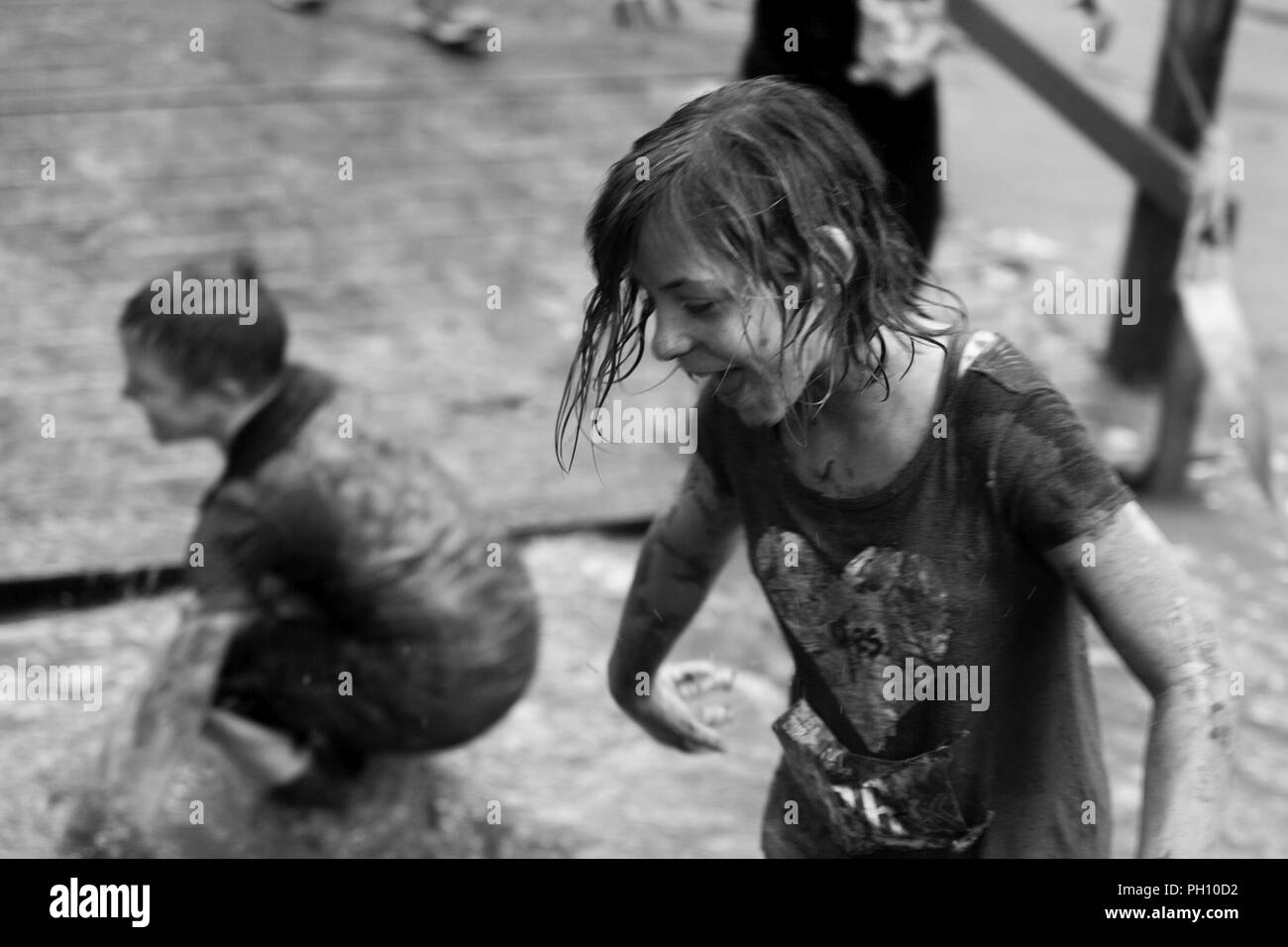 Participants run during the annual Marine Corps Marathon (MCM) Run A Muck race at Marine Corps Base Quantico, Va., June 23, 2018. The Run A Muck is the MCM's messiest mud and obstacle course, consisting of a four mile trail with 21 challenges to include body weight exercises, rope climbs, and mud pits. - Stock Image