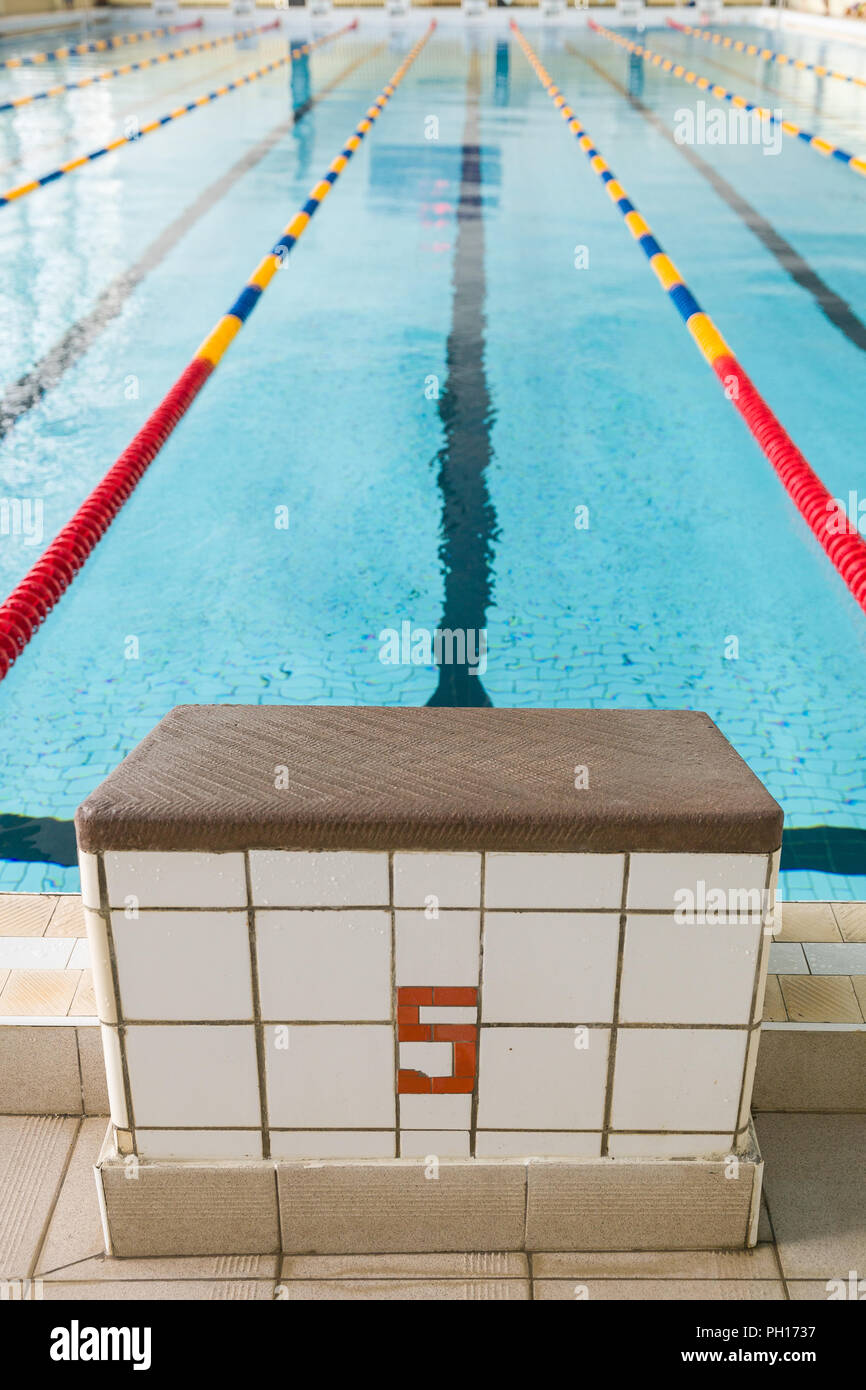 Starting blocks and lanes in a swimming pool. Edge of ...