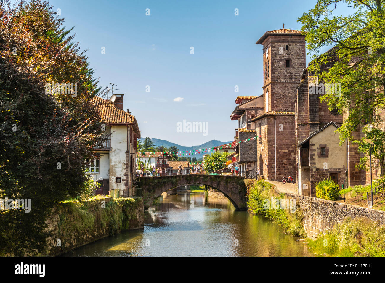 View of the river Nive on its way through the village of Saint Jean Pied de Port and in the background the Pyrenees. France. - Stock Image