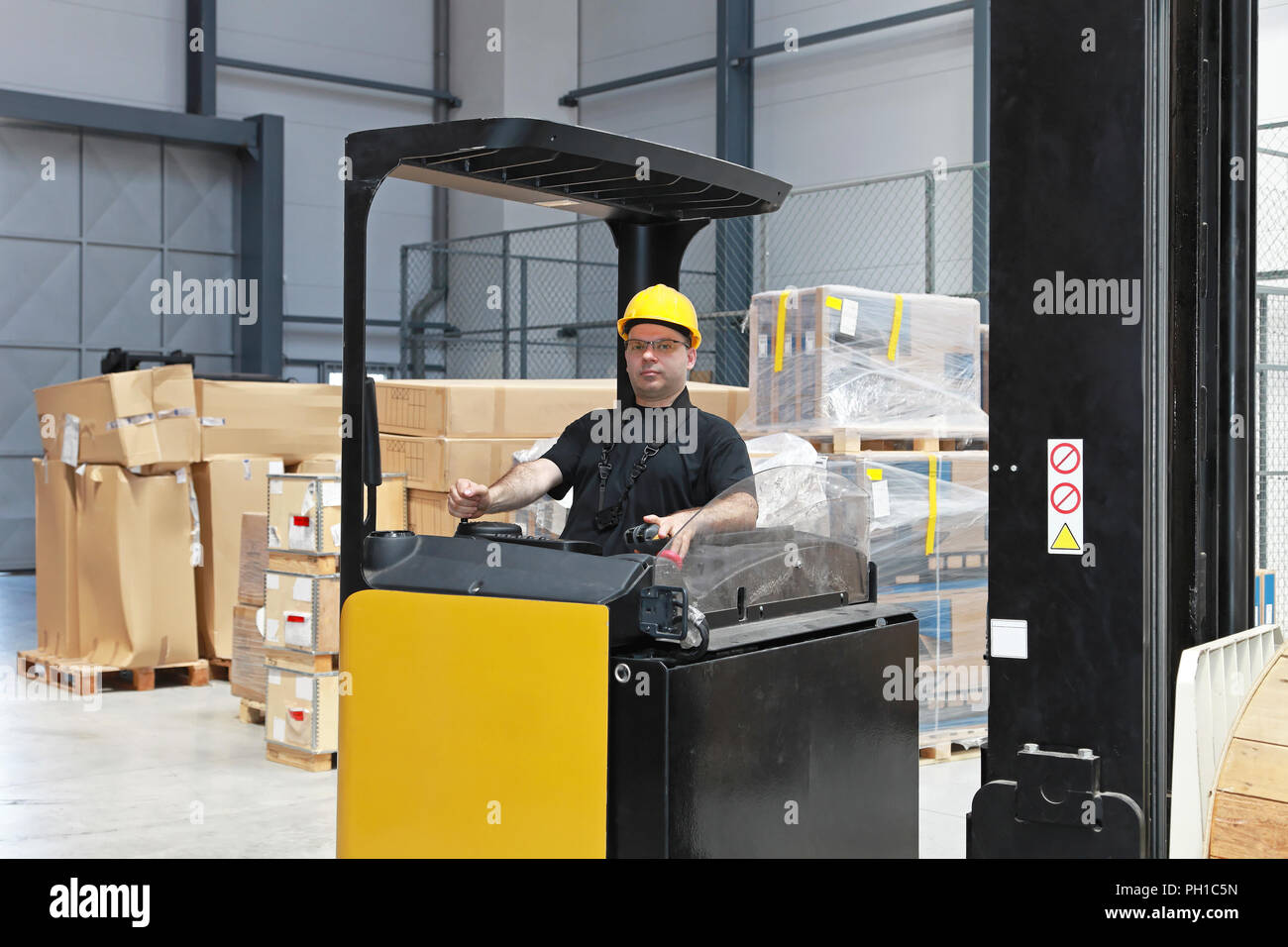 Forklift driver with yellow helmet in distribution warehouse - Stock Image