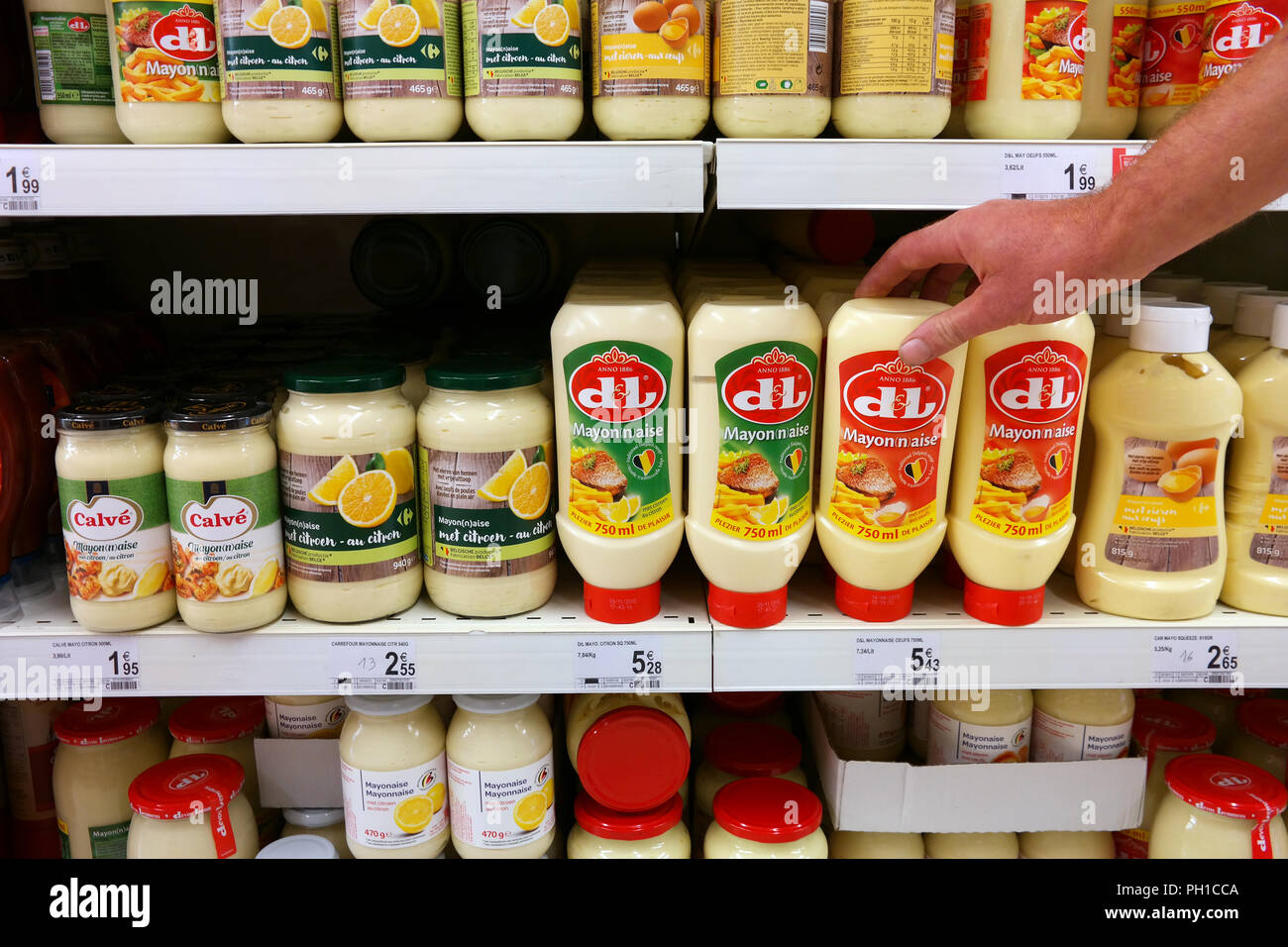 Shelves with various brands of Mayonnaise in a store - Stock Image