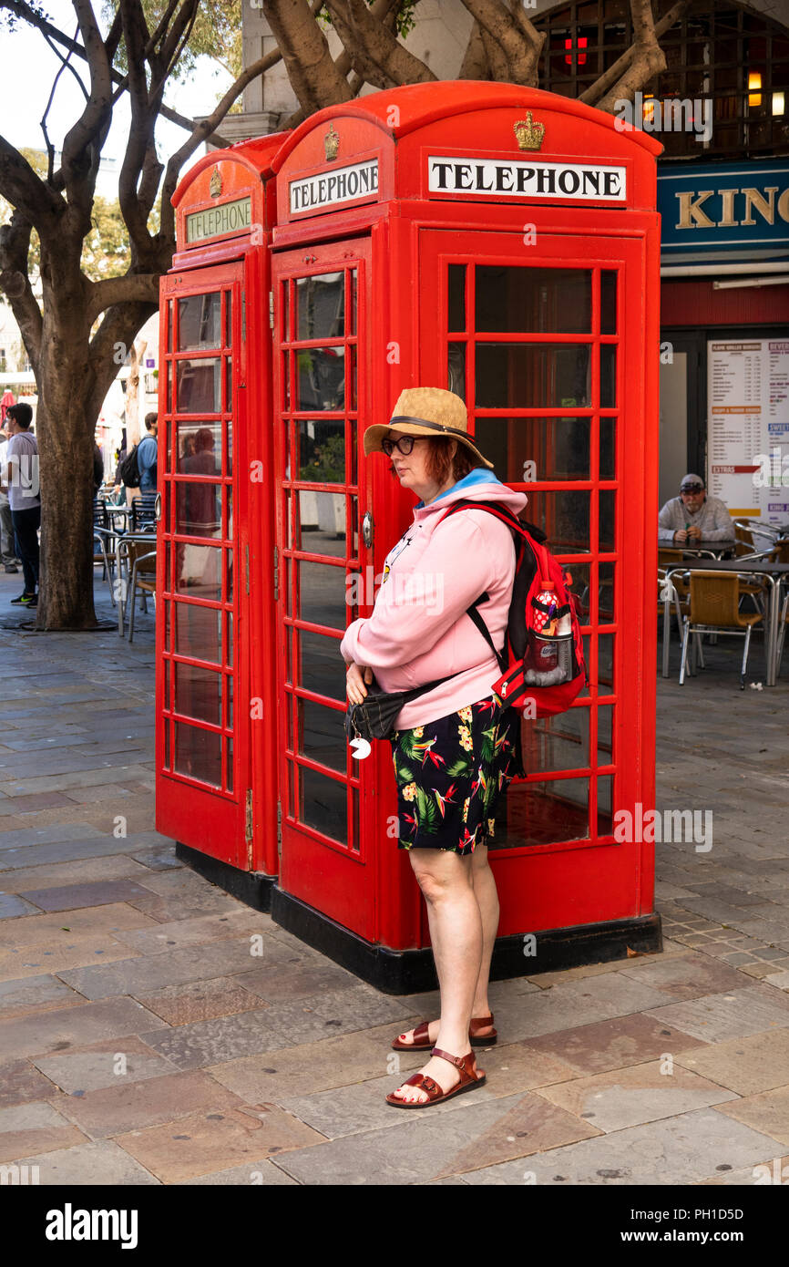 Gibraltar, Casemates Square, tourist beside two British K6 red phone boxes - Stock Image
