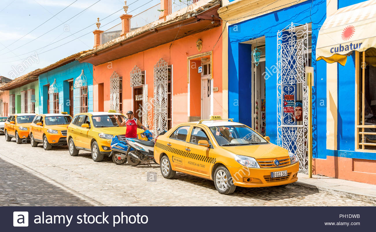 Line of taxis waiting for tourists in a cobblestone street of the colonial Trinidad, a Unesco World Heritage Site - Stock Image