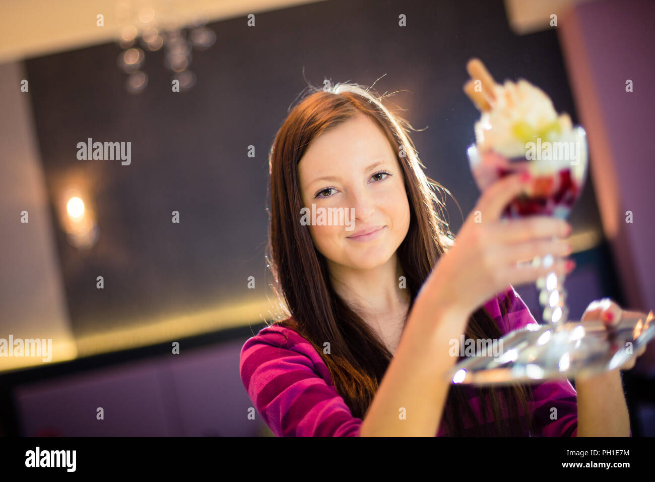 Cute young woman in an ice cream parlor, taking her ice-cream from the counter Stock Photo
