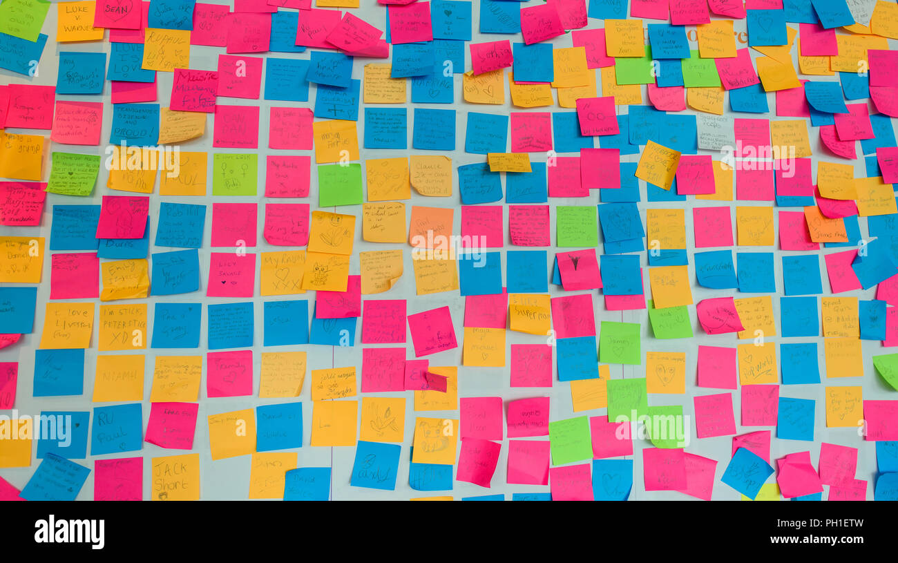 LiA Wall covered in post-it notes with various personal messages of love, peace and relationships by adults and children at the Museum of Liverpool - Stock Image