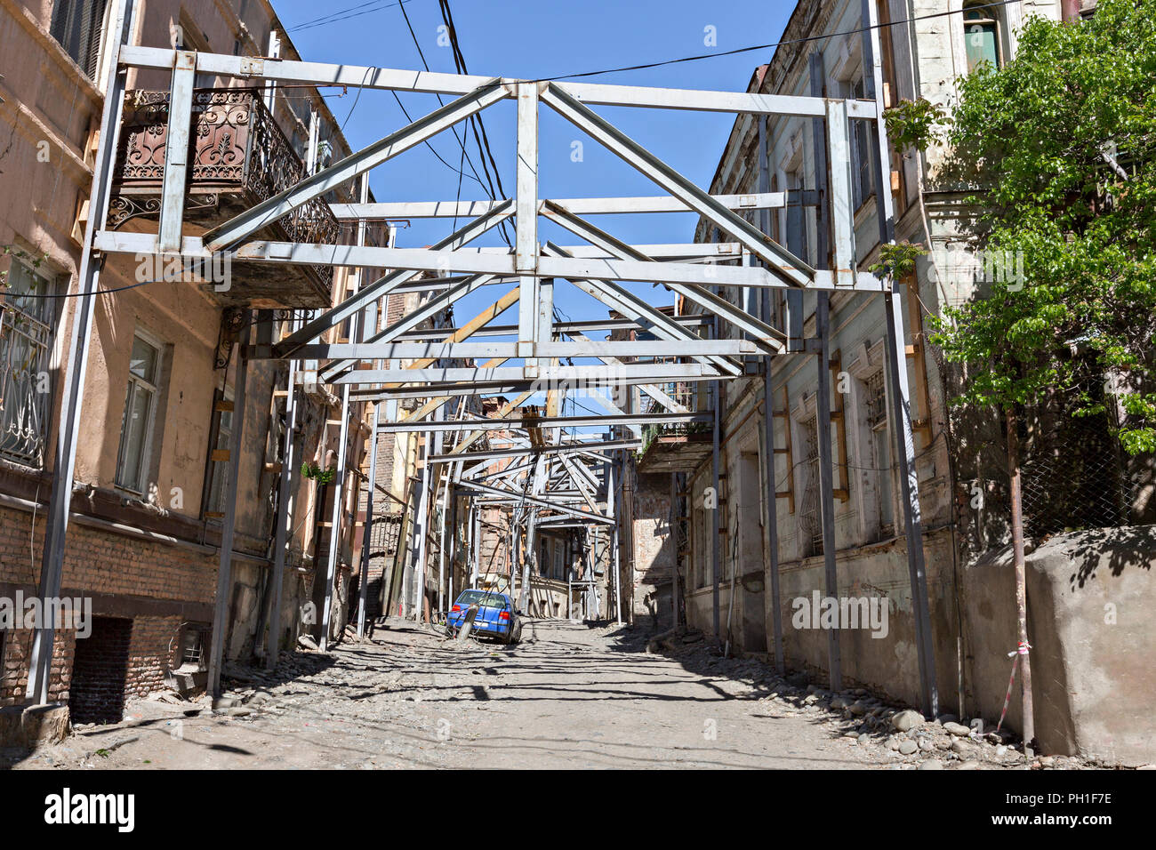 Supporting the old houses with steel bars for restoration in the old part of Tbilisi, Georgia. - Stock Image