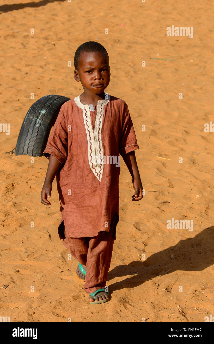 LAMPOUL DESERT village, SENEGAL - APR 23, 2017: Unidentified Senegalese little boy in traditional suit walks in a village near the Lampoul Desert - Stock Image