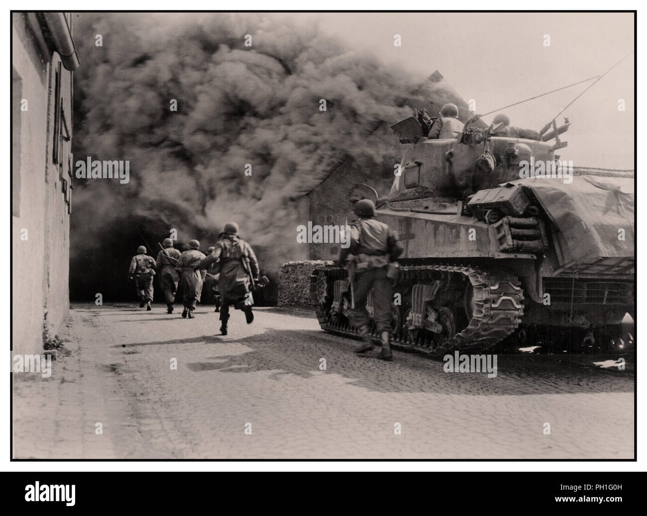 WW2 GI Soldiers of the 55th Armored Infantry Battalion Third Army and M4 Sherman tank of the 22nd Tank Battalion, advance move through smoke filled street. Wernberg, Germany. April 22, 1945 - Stock Image
