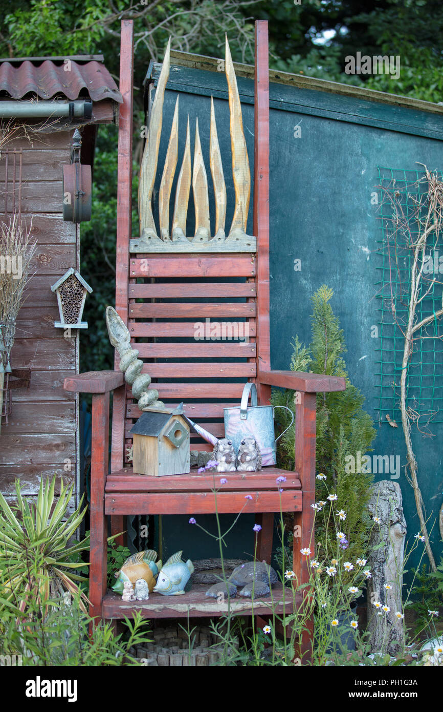 Large oversized wooden garden chair, handmade DIY for ornamental use. It is an expression of individual creativity in an outside space. - Stock Image