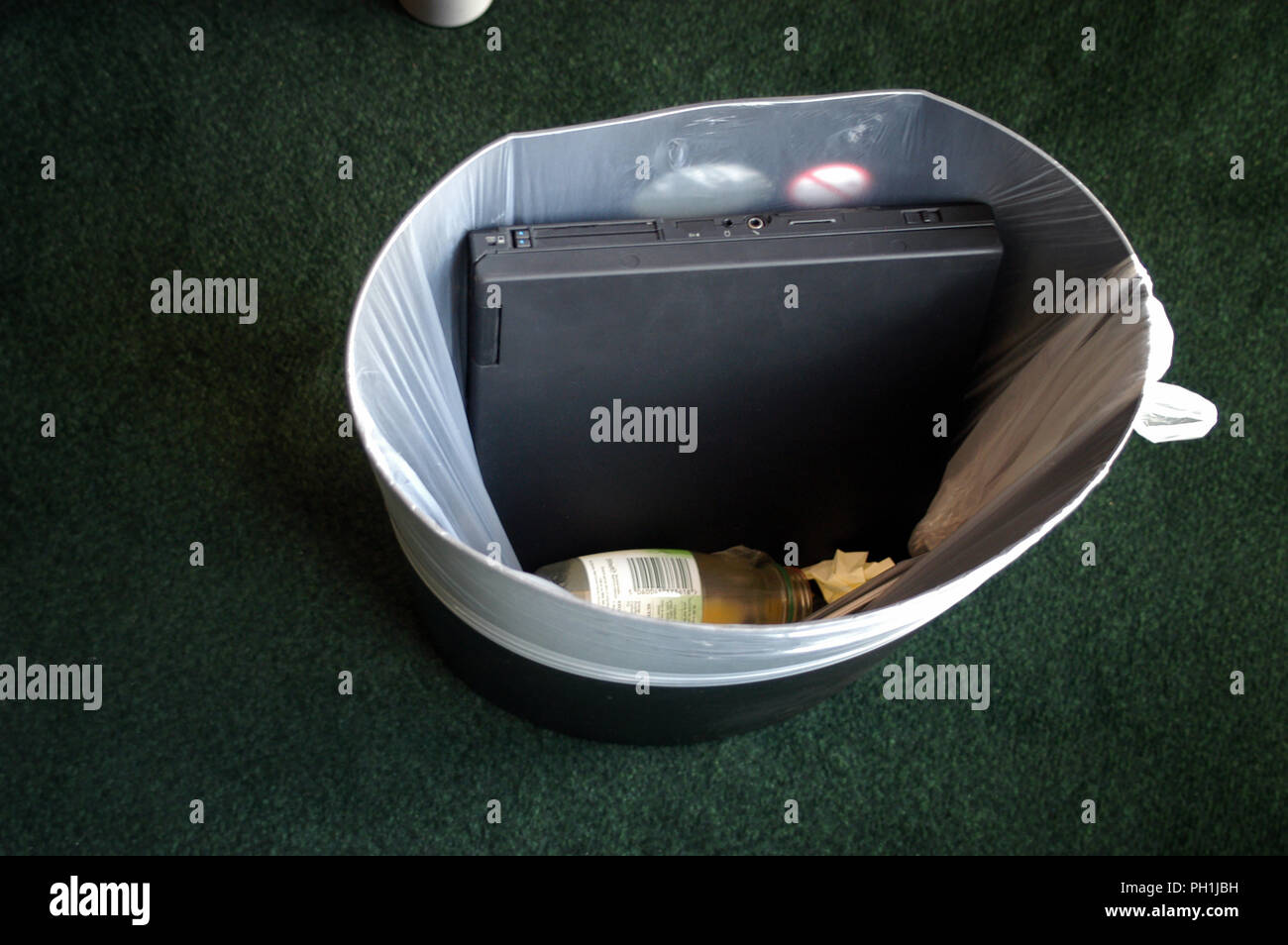 Old Laptop thrown in a waste bin at the office in the City area of London, England - Stock Image