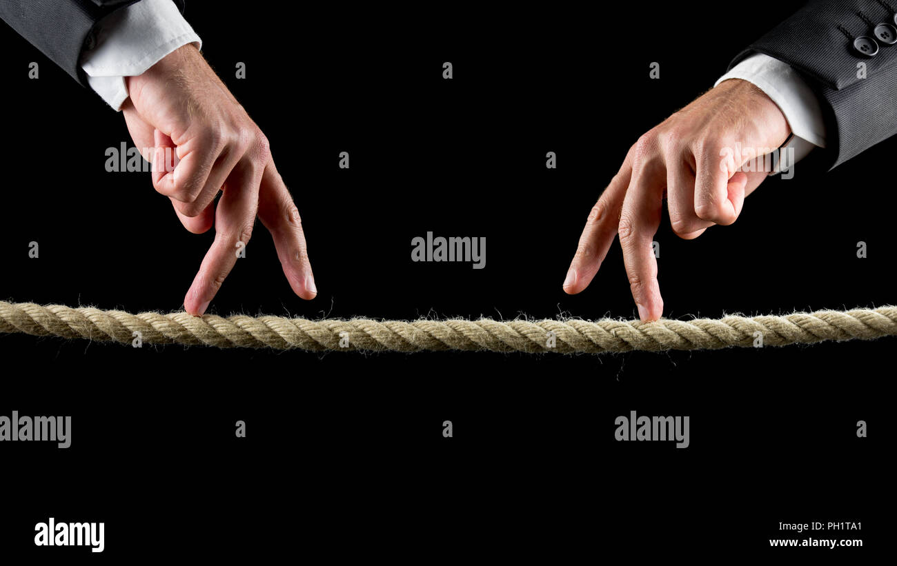 Close-up of two male hands wearing business suit and making the walking sign toward each other on a rope, concept of meeting and encounter, with copy  Stock Photo