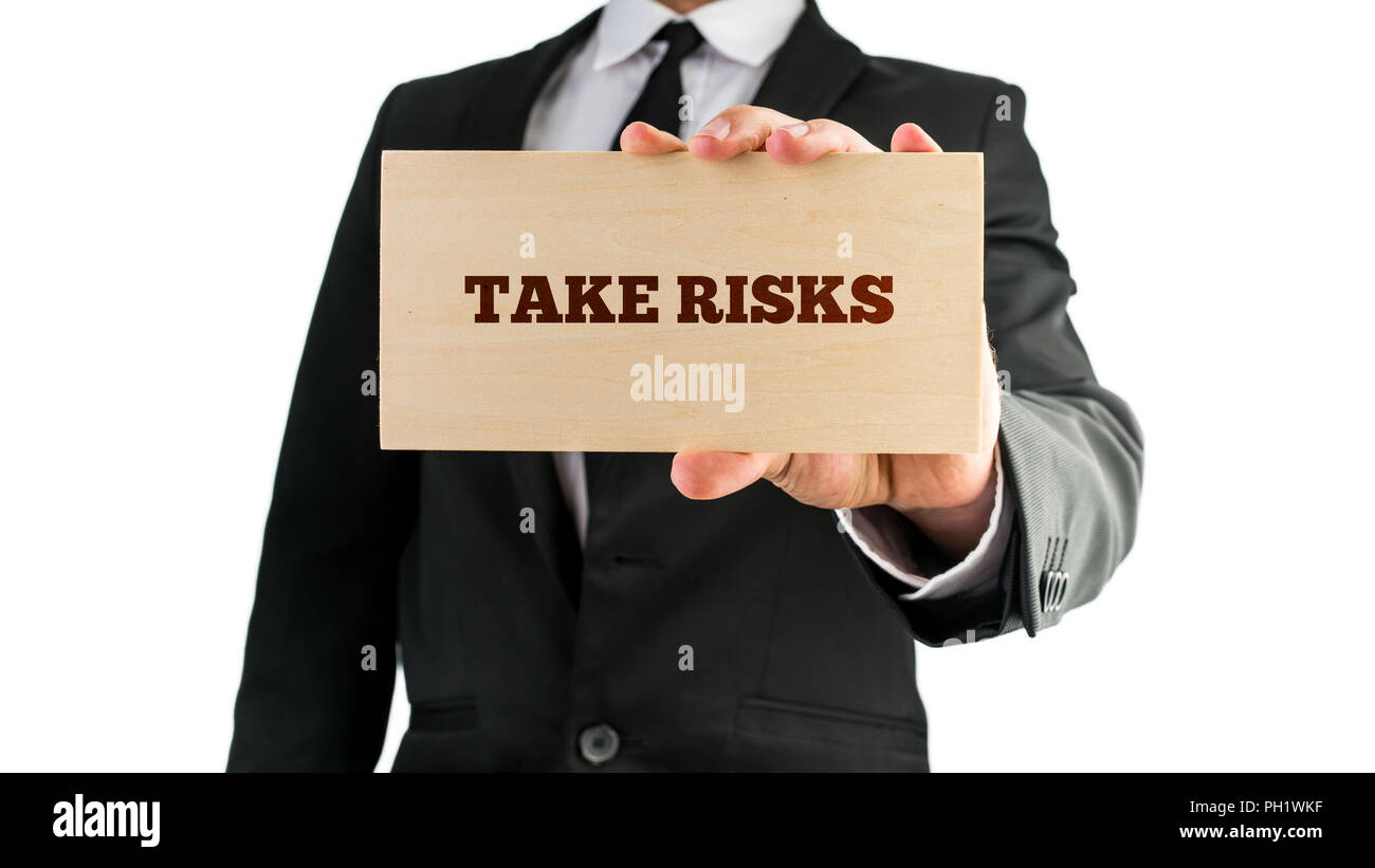 Businessman holding a rectangular wooden sign saying Take risks. Over white background. - Stock Image
