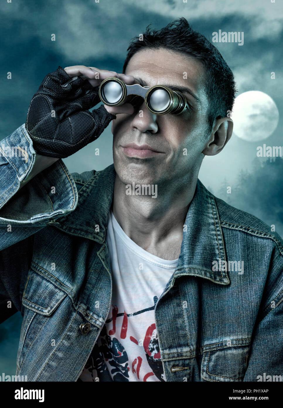 Man looking far away with his old binoculars at night. - Stock Image