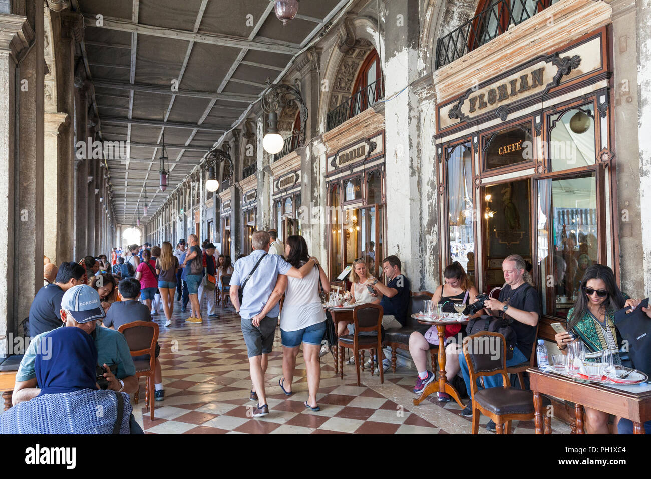 People dining at tables outside in shade under the arcade at Caffe Florian, Piazza San Marco, San Marco, Venice, Veneto, Italy during the European hea - Stock Image