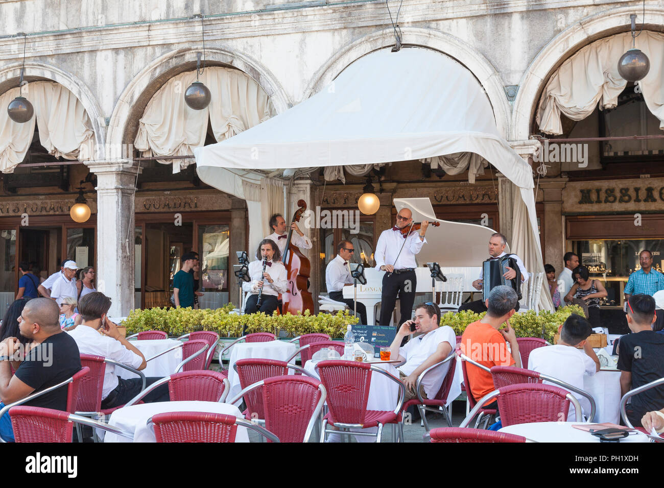 Live music performance at Caffe Ristorante Quadri, Piazza San Marco, Venice, Veneto, Italy with tourists seated  at outdoor tables enkoying the shade - Stock Image