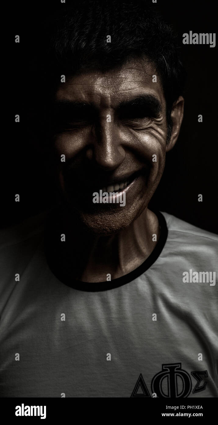 Distressing psychopath smiles at you from the shadows. - Stock Image