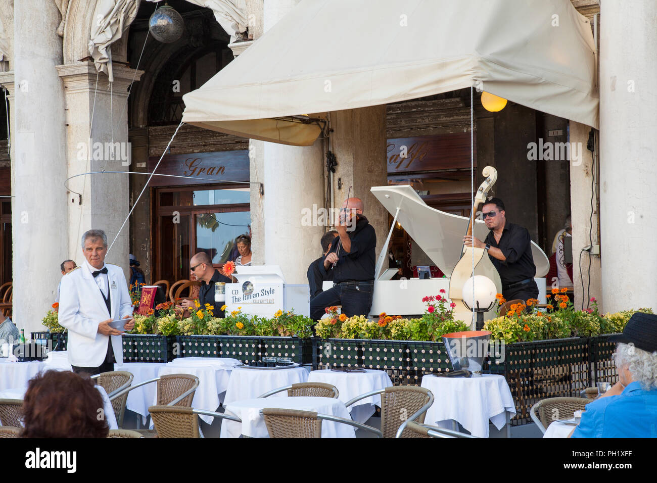 People listening to classical music at Gran Caffe Chioggia, Piazza San Marco, Venice, Veneto, italy while enjoying drinks. Live performance of Italian Stock Photo