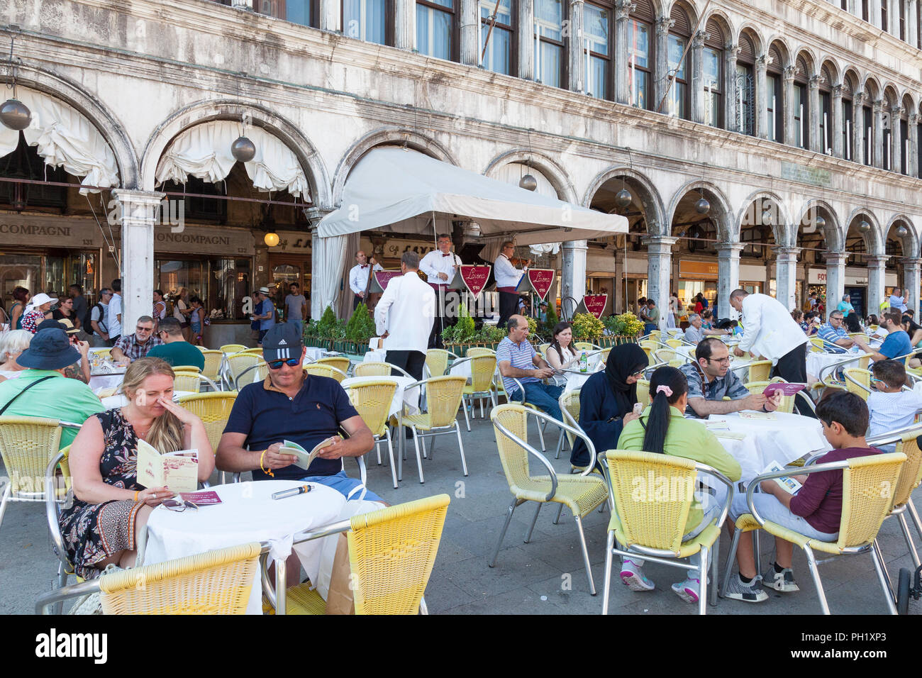 Tourists eating and drinking at Caffe Lavena, Piazza San Marco, Venice, Veneto, Italy while listening to a live music performance at outdoor tables - Stock Image