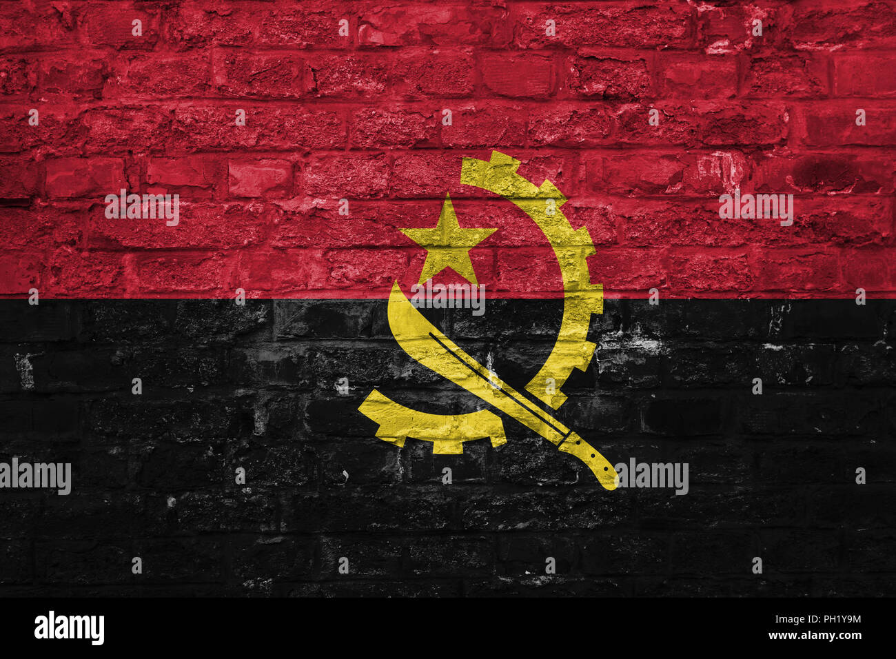 Flag of Angola over an old brick wall background, surface - Stock Image