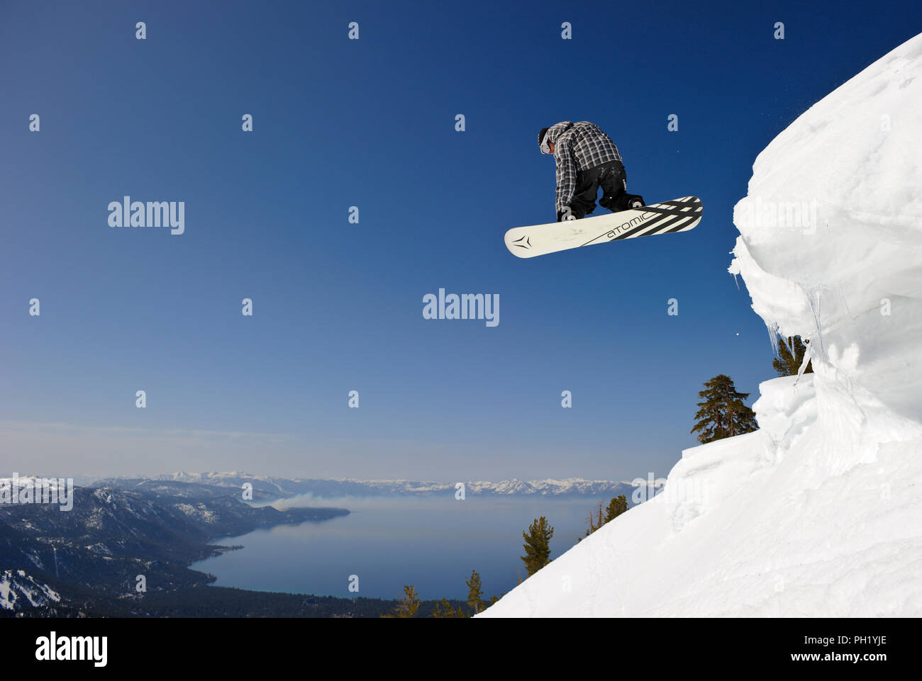 Snowboarder Nick Langkamp on top of Incline Peak with North Lake Tahoe in the background on a clear day. Stock Photo