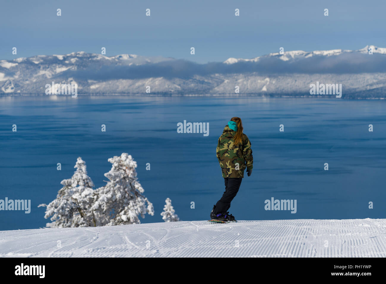 A snowboarder rides into Lake Tahoe as viewed from Diamond Peak ski resort in Incline Village after a snow storm. Stock Photo