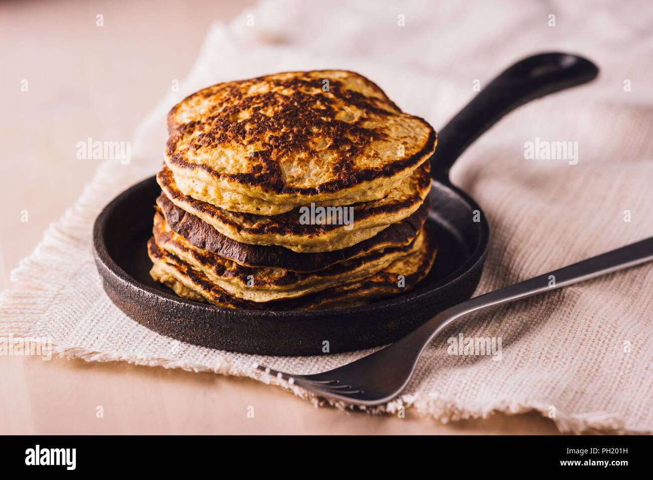 Pile of homemade pancakes freshly made on a small pan, ready to eat - Stock Image