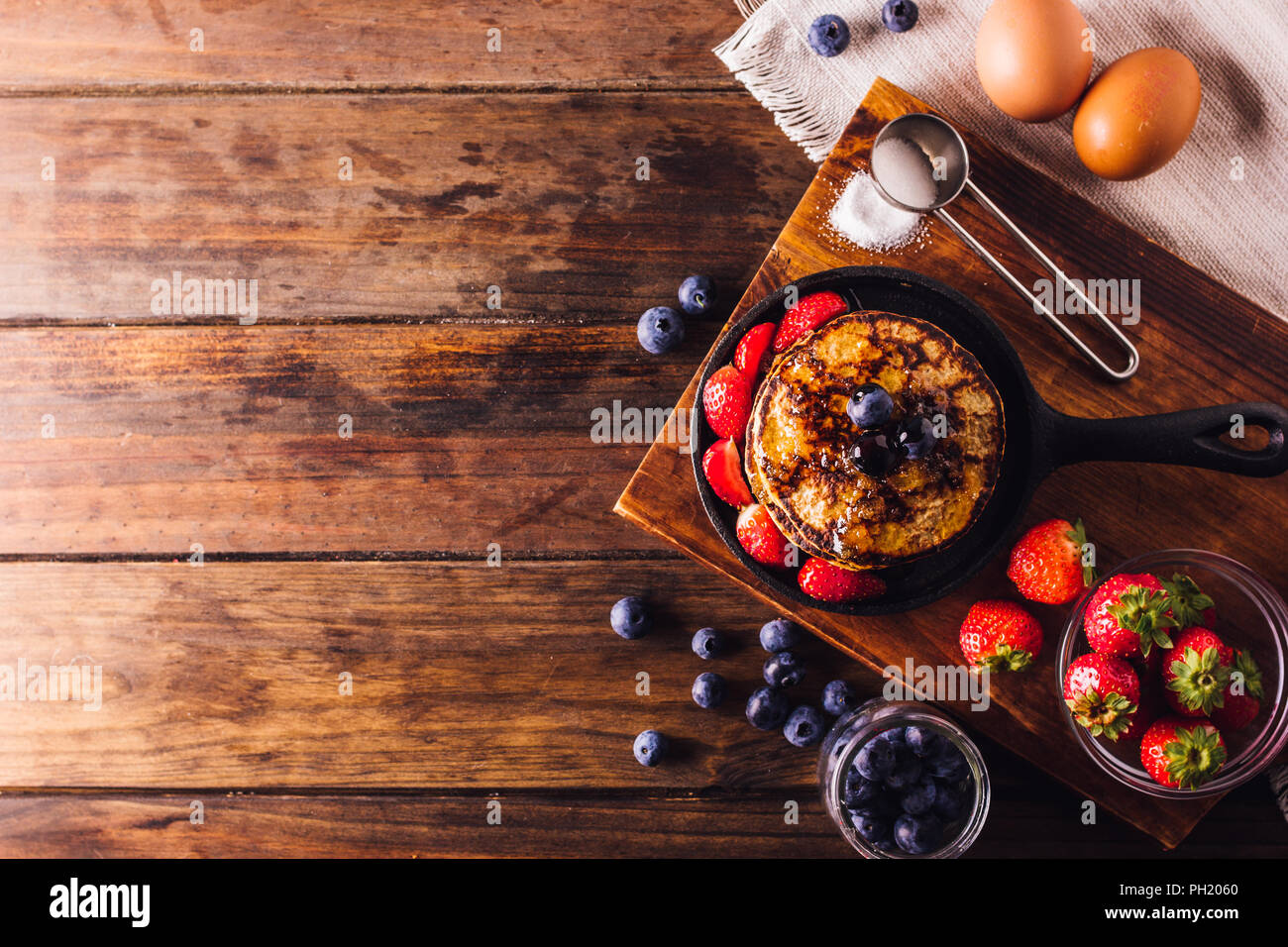 Top View of Delicious breakfast of pancakes served with strawberries and blueberries, On the left side a Copy space to logo or text - Stock Image