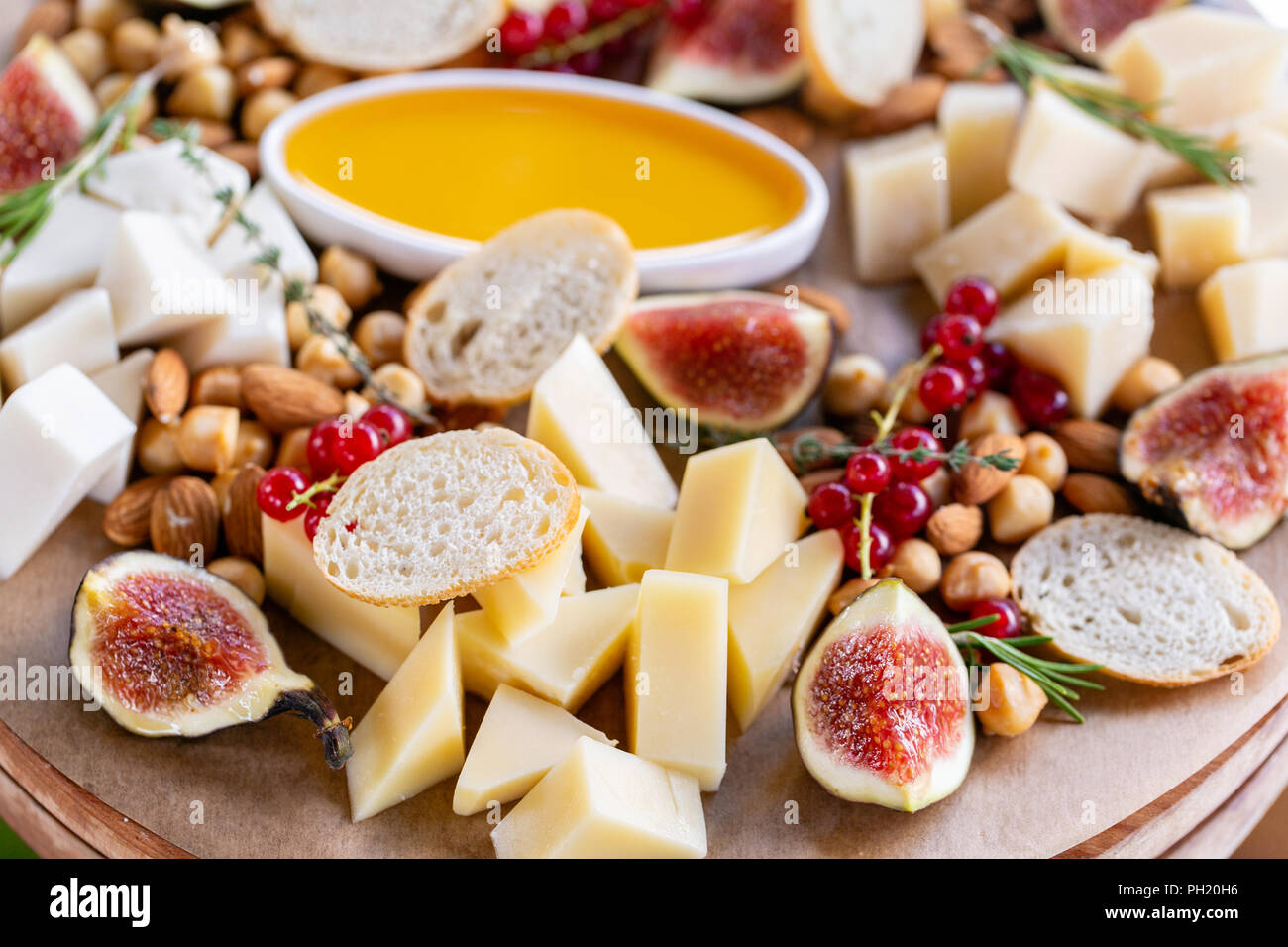 Light Italian snacks. A buffet table at a dinner party. Cheese plate. Delicious cheese mix on wooden table. Tasting dish on a wooden plate. Food for wine. - Stock Image