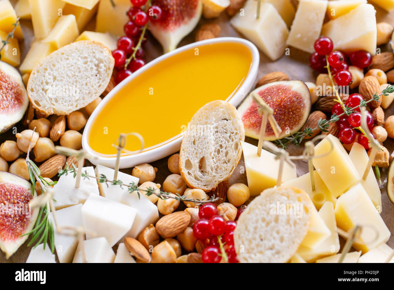Cheese plate. Delicious cheese mix with baguette croutons, red currant, sweet figs, almond, honey on wooden table. Tasting dish on a wooden plate. Food for wine. Goat cheese, Parmesan, Gouda - Stock Image