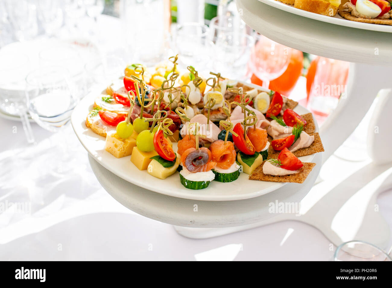 solemn banquet. Lot of glasses champagne or wine on the table in restaurant. buffet table with lots of delicious snacks. canapes, bruschetta, and little desserts on wooden plate board - Stock Image