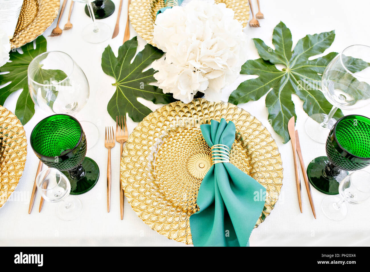 Beautiful banquet hall under a tent for a wedding reception. Interior of a wedding tent decoration ready for guests. Decor flowers. Green theme - Stock Image