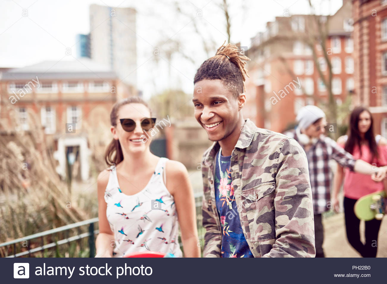 Teenage couple walking in park Stock Photo