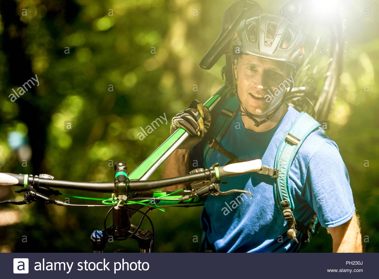 Man carrying mountain bike in forest - Stock Image