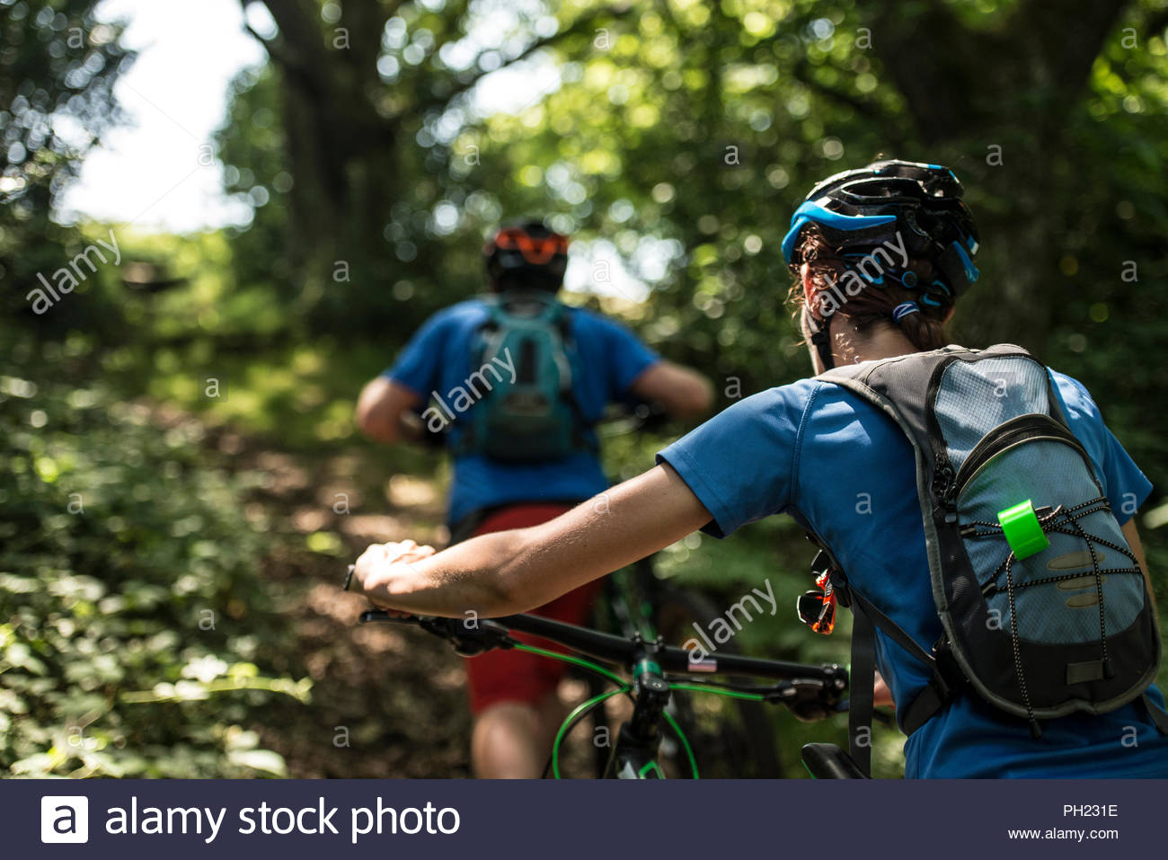 Couple pushing mountain bikes uphill in forest - Stock Image