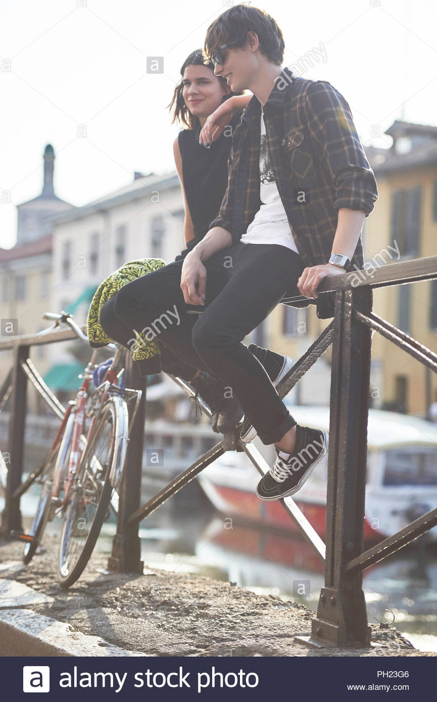 Teenage couple sitting on railing - Stock Image