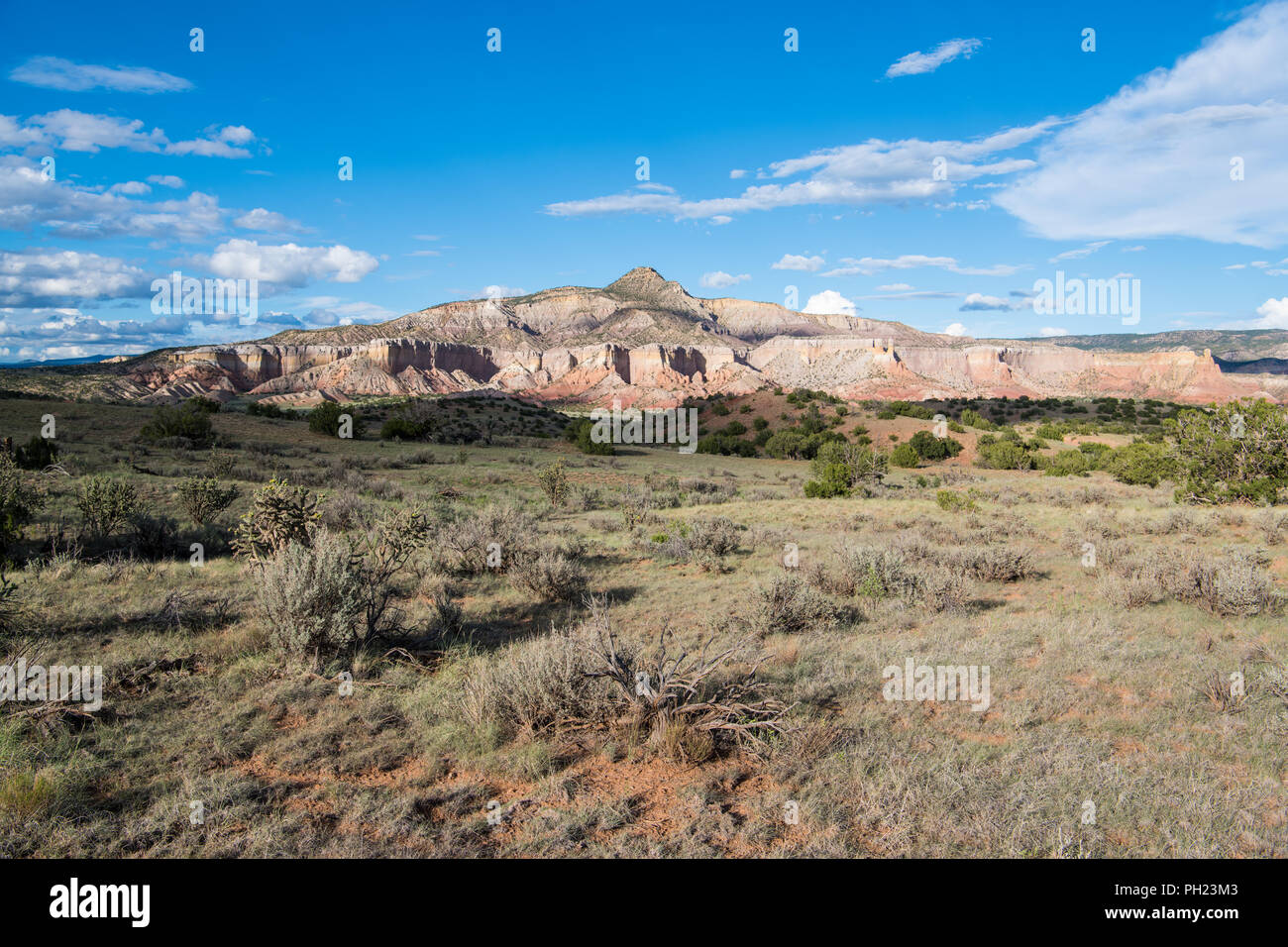 Mountain peak, colorful cliffs, and vast desert landscape underneath dramatic blue sky and clouds at Ghost Ranch near Abiquiu, New Mexico - Stock Image