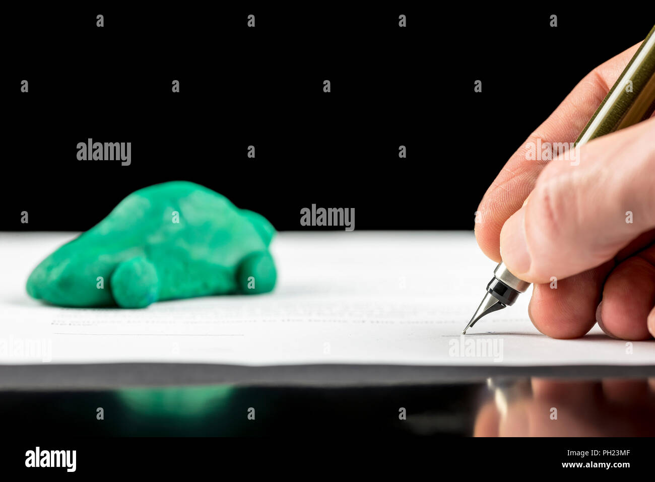 Conceptual image of the hand of a man signing a contract for the lease or purchase a green eco-friendly fuel efficient, electric or hybrid car with re - Stock Image